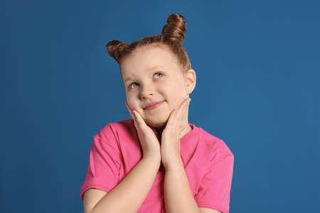 Portrait of little girl on blue background