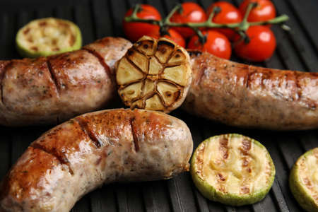 Cooking delicious fresh sausages with vegetables on modern grill, closeup Stock Photo