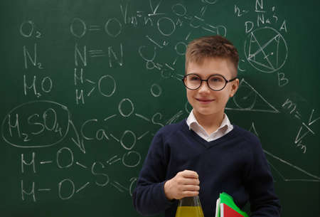 Schoolboy holding flask near chalkboard with chemical formulas