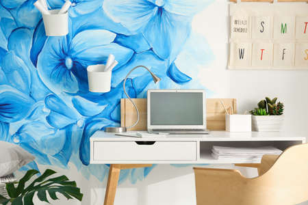 Stylish workplace with blue flowers painted on wall. Floral pattern in living room interior 스톡 콘텐츠