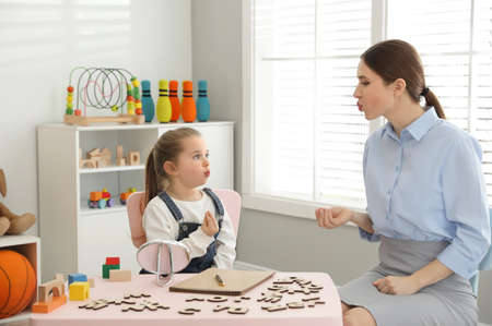 Speech therapist working with little girl in office Imagens