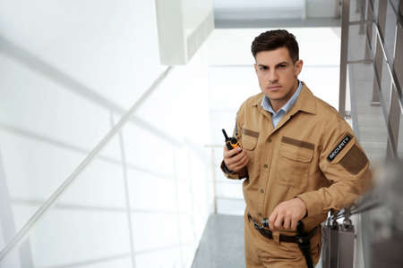 Professional security guard with portable radio set on stairs. Space for text