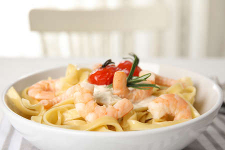 Delicious pasta with shrimps on table, closeup