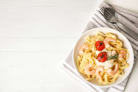 Delicious pasta with shrimps served on white wooden table, top view. Space for text 写真素材