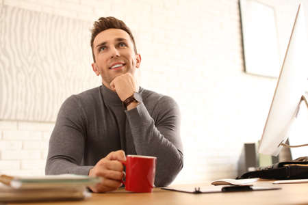 Young man with cup of drink relaxing at table in office during break Zdjęcie Seryjne