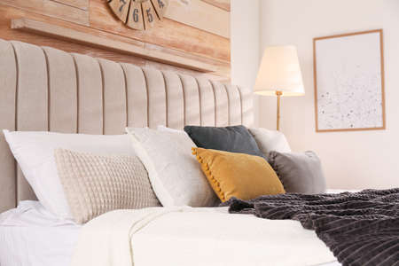 Comfortable bed with pillows in modern room interior