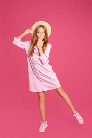 Full length portrait of preteen girl in hat on pink background Stock Photo