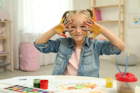 Cute little child painting with palms at table