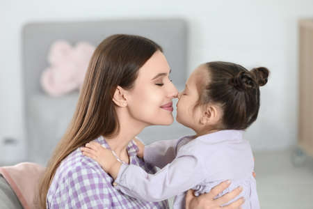 Young mother with little daughter at home