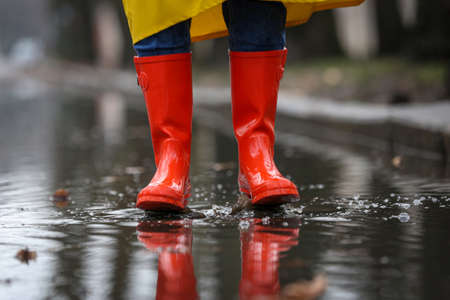 Woman jumping in puddle outdoors on rainy day, closeup