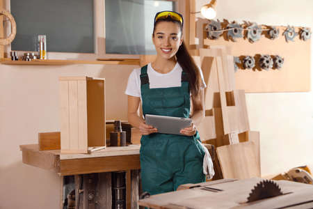 Professional carpenter in uniform with tablet near workbench Standard-Bild