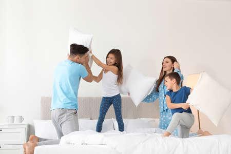 寝室で枕の戦いを持つ幸せな家族 写真素材