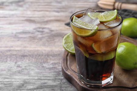 Glass of fresh Cuba Libre cocktail on wooden table, closeup. Space for text