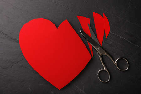 Cut paper heart and scissors on black stone background, flat lay. Relationship problems concept Stockfoto