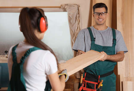 Professional carpenters with wooden plank in workshop Stockfoto