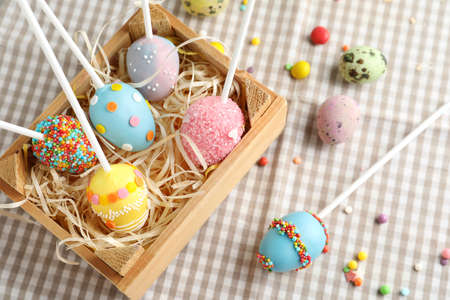 Delicious sweet cake pops in wooden crate on table. Easter holiday