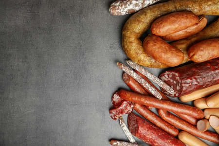 Different types of sausages on grey background, flat lay. Space for text Фото со стока