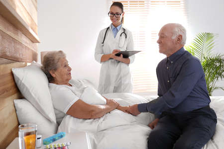 Senior couple and doctor in modern hospital
