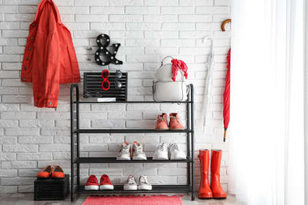 Shelving rack with stylish women's shoes and accessories near white brick wall indoors Foto de archivo