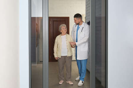 Doctor with senior patient at modern hospital Stock Photo
