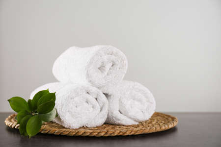 Clean rolled bath towels, green branch and wicker mat on dark grey table