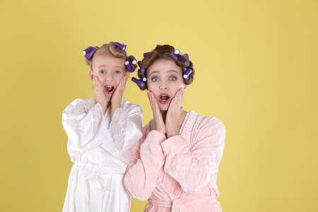 Emotional mother and daughter with curlers on yellow background