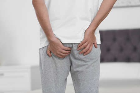 Man suffering from hemorrhoid in bedroom, closeup 스톡 콘텐츠