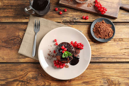Delicious warm chocolate lava cake with mint and berries on wooden table, flat lay