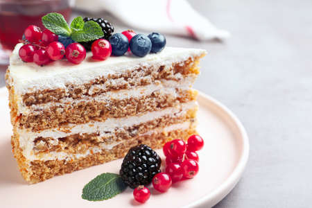 Tasty cake with berries on grey table, closeup Reklamní fotografie