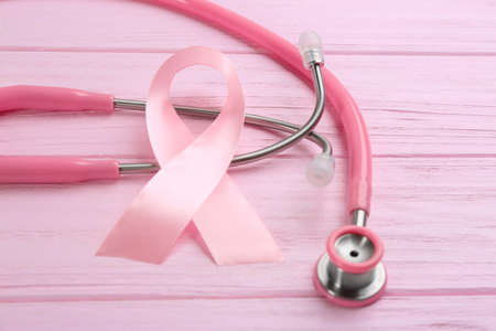 Pink ribbon and stethoscope on wooden background, closeup. Breast cancer concept