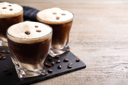 Glasses of tasty cocktail with coffee beans on wooden table, closeup Banque d'images