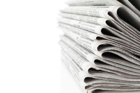Stack of newspapers on white background, closeup. Journalists work