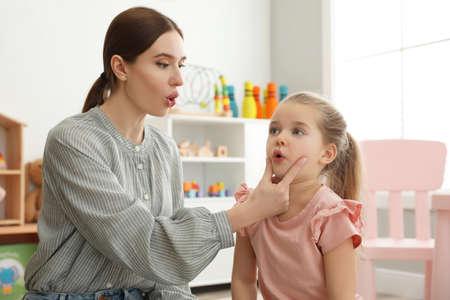 Speech therapist working with little girl in office Foto de archivo