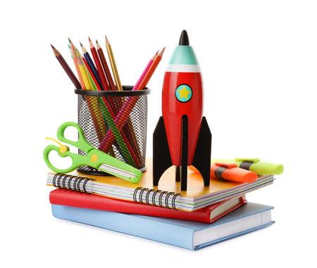 Cohete de juguete brillante y útiles escolares sobre fondo blanco. Foto de archivo