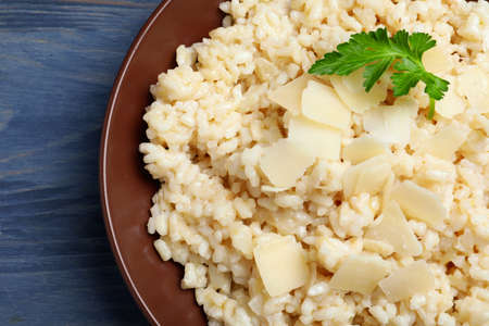 Delicious risotto with cheese on blue wooden table, closeup Imagens
