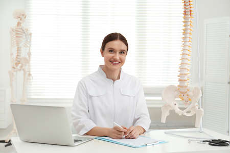 Female orthopedist with laptop near human spine model in office