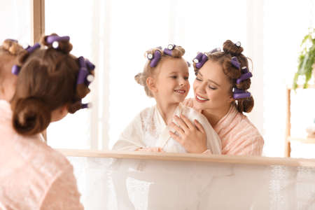 Happy mother and daughter with curlers near mirror in bathroom
