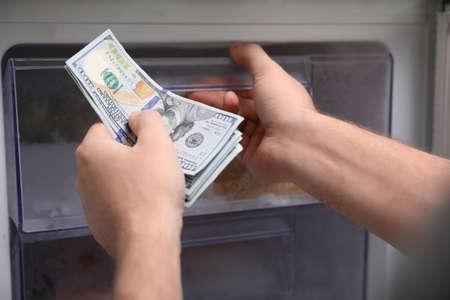 Man hiding money in refrigerator, closeup. Financial savings Zdjęcie Seryjne