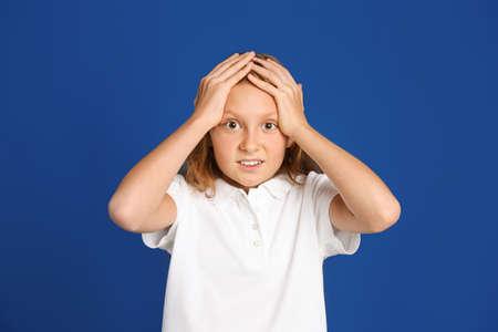 Portrait of emotional preteen girl on blue background