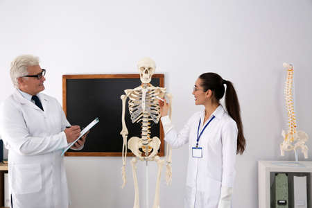 Medical student and professor studying human skeleton anatomy in classroom Stock Photo