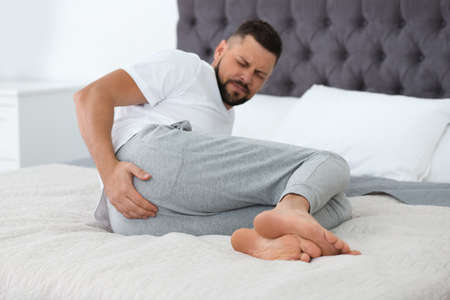 Man suffering from hemorrhoid on bed at home, focus on hand