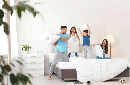 Happy family having pillow fight in bedroom