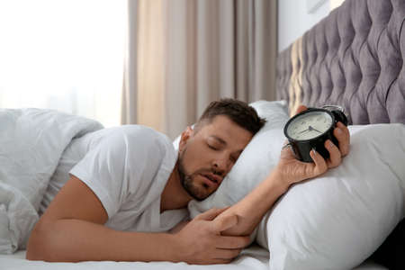 Man with alarm clock sleeping at home in morning