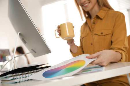 Professional designer working at table in office, closeup