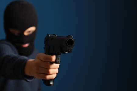 Man in mask holding gun against dark blue background, focus on hand. Space for text 写真素材
