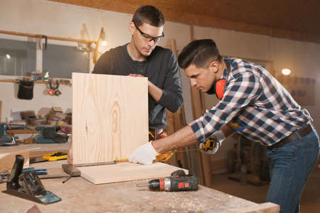 Professional carpenters working with wooden boards in workshop Stockfoto