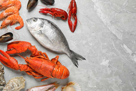Poisson frais et fruits de mer sur table en marbre, mise à plat. Espace pour le texte