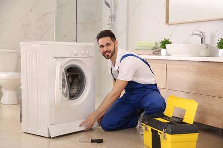 Professional plumber repairing washing machine in bathroom Foto de archivo