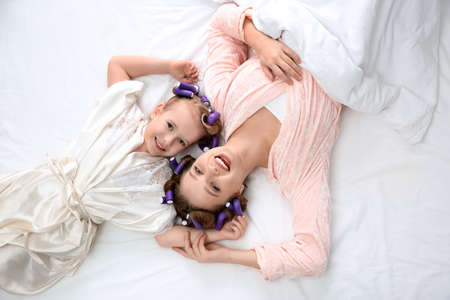 Happy mother and daughter with curlers lying on bed, top view