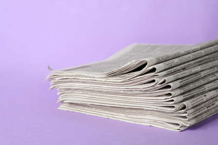 Stack of newspapers on light violet background. Journalist's work